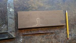 de nieuwe kam van de rebab wordt overgetrokken van het resterende stukje hout